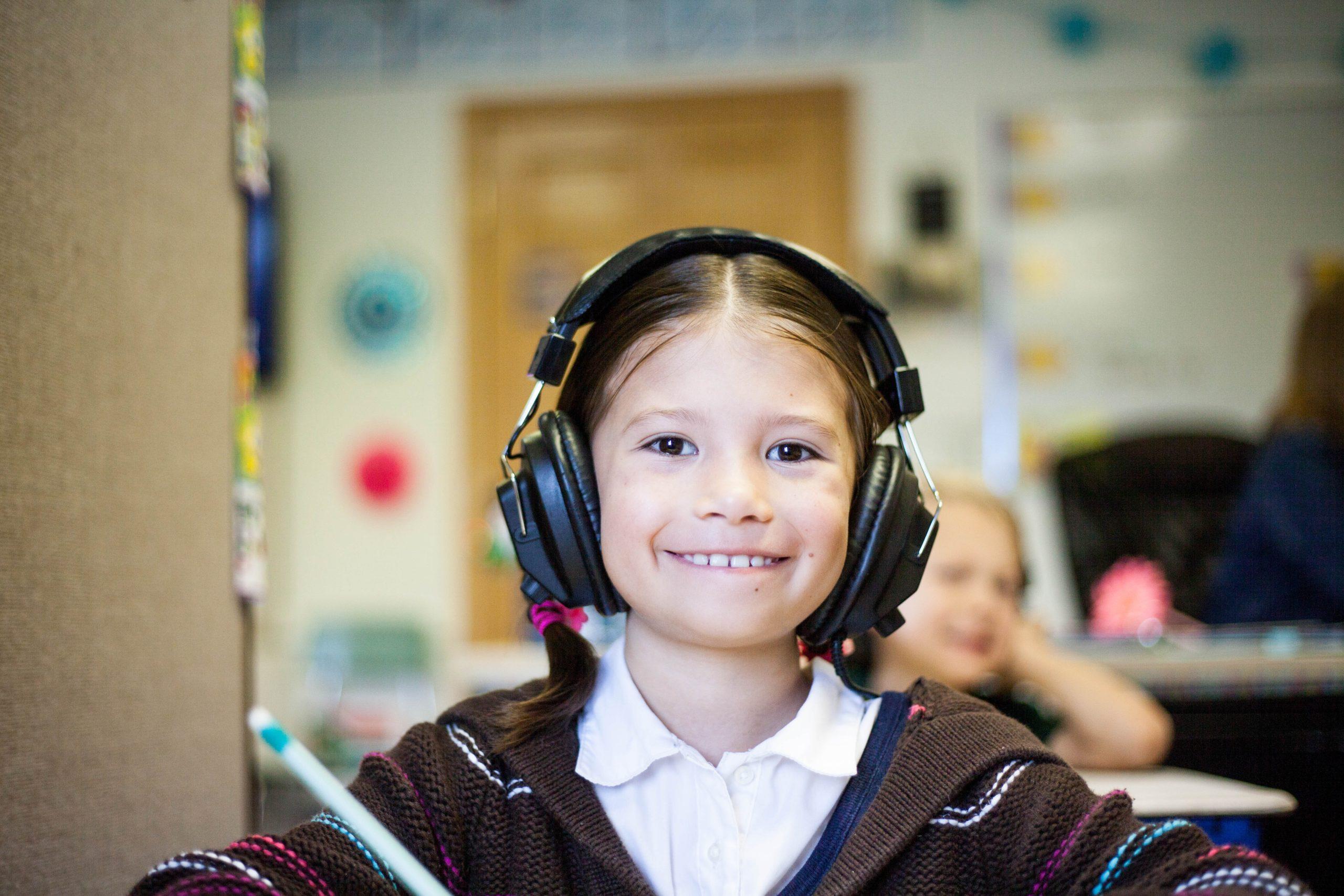 Ein kleines Mädchen lächelt in die Kamera. Sie trägt Kopfhörer.