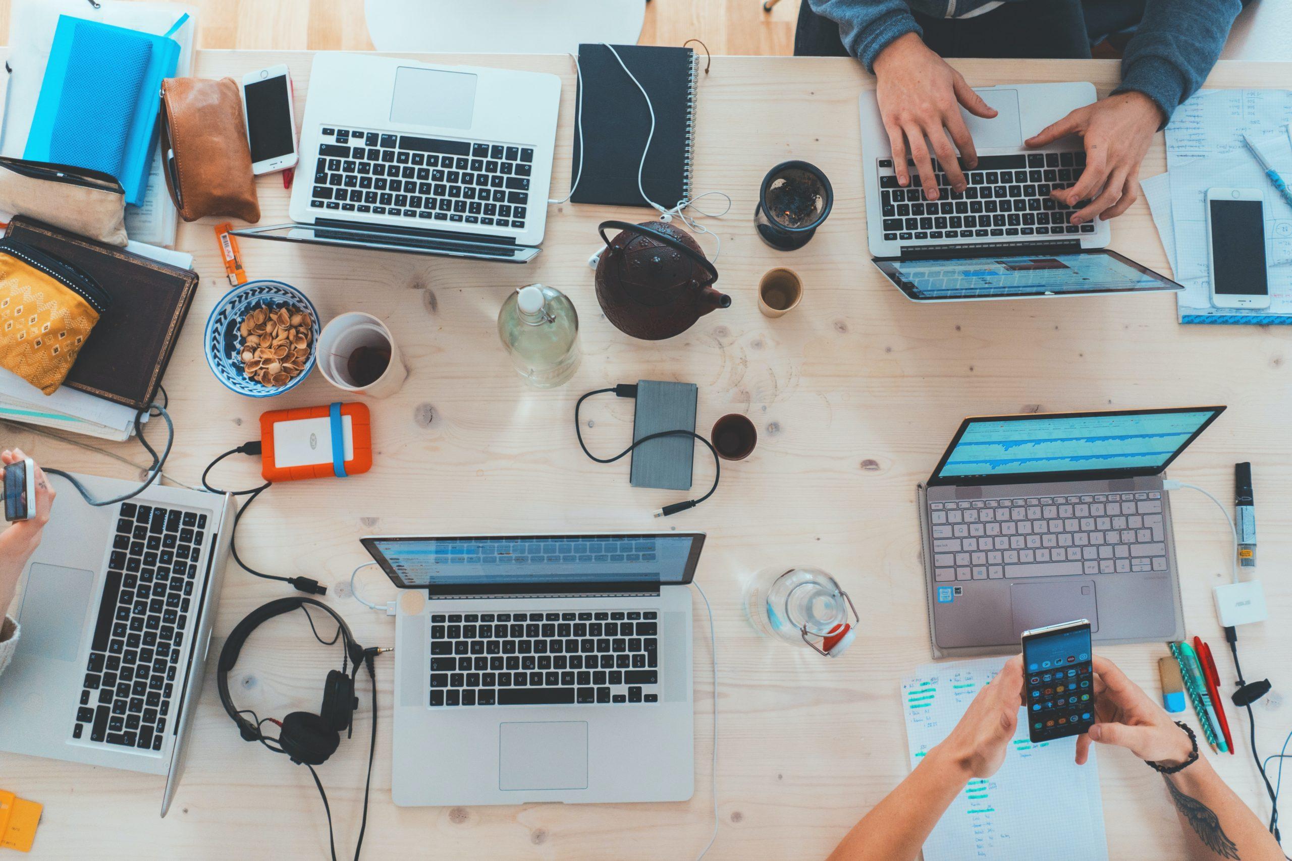 Das Bild zeigt einen Schreibtisch mit vier Laptops und Büro-Utensilien.