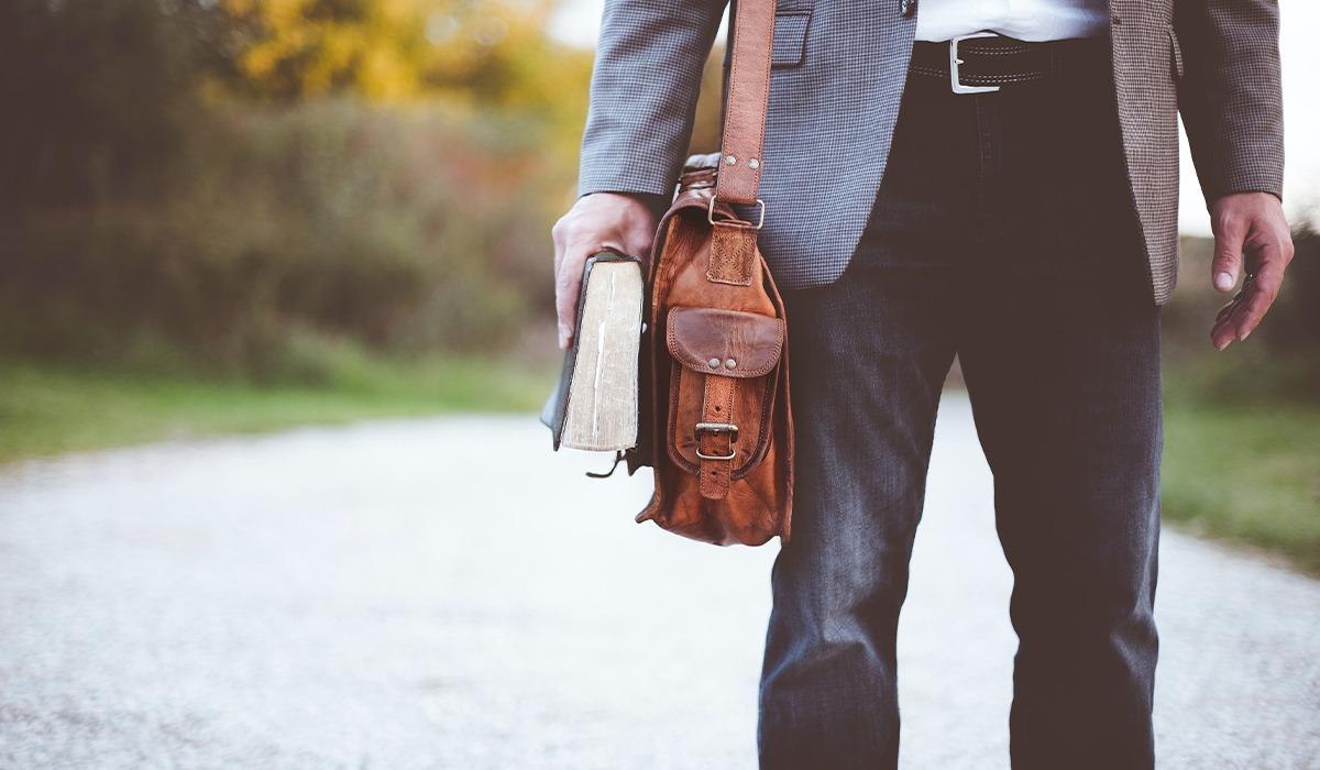 Das Foto zeigt einen Mann. Der Mann trägt eine Aktentasche. In der Hand hält er ein Buch. Das Foto verweist auf Arbeitsstellen bei Media Smart e. V.