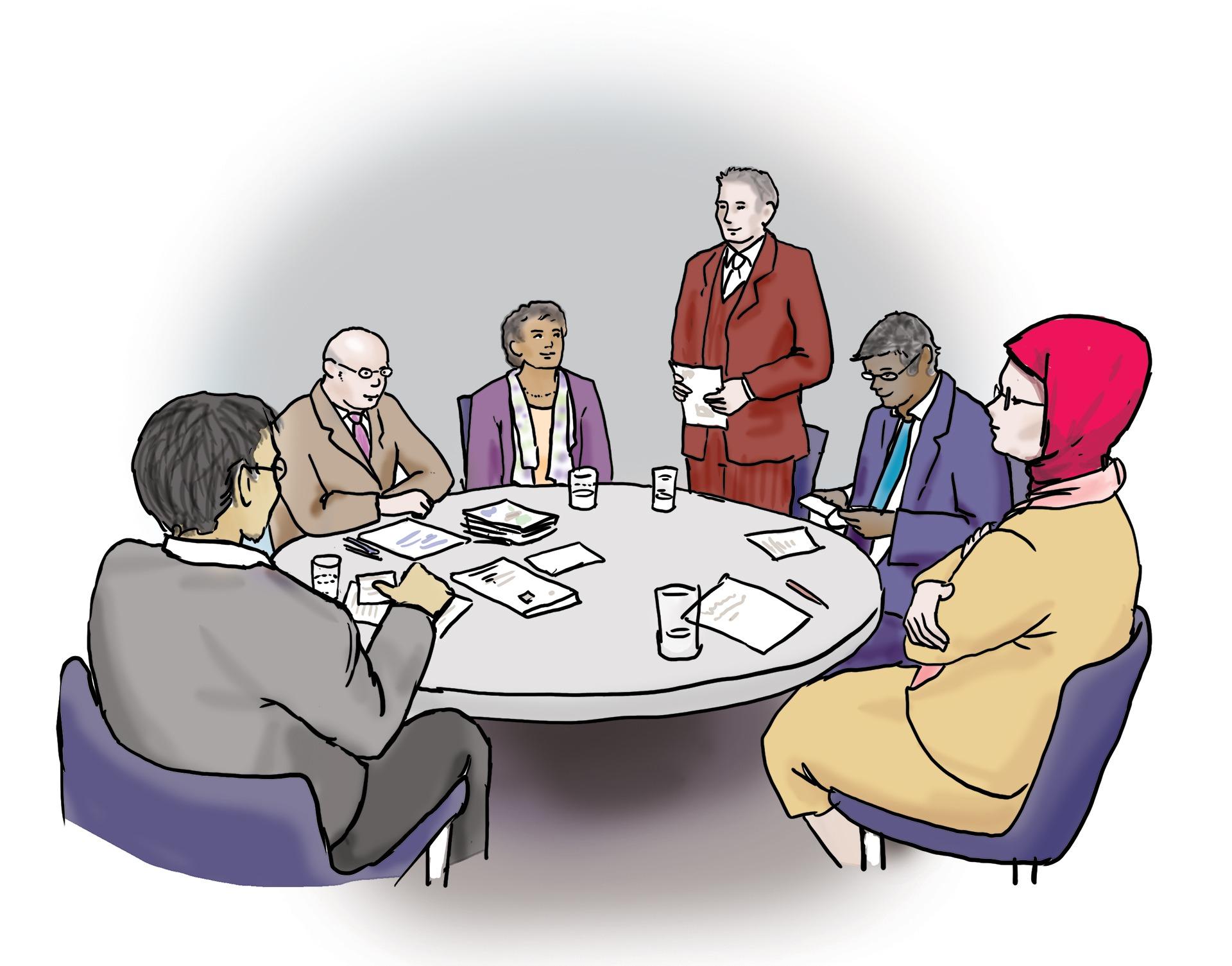 Das Bild zeigt eine Gruppe von Menschen. Sie sitzen an einem runden Tisch.