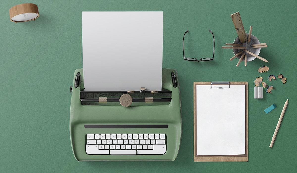 Das Bild zeigt eine Schreibmaschine, einen Block und verschiedene Bleistifte auf grünem Grund.
