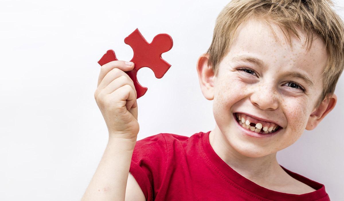 Das Bild zeigt einen Jungen. Er hat ein rotes Puzzleteil in der Hand.