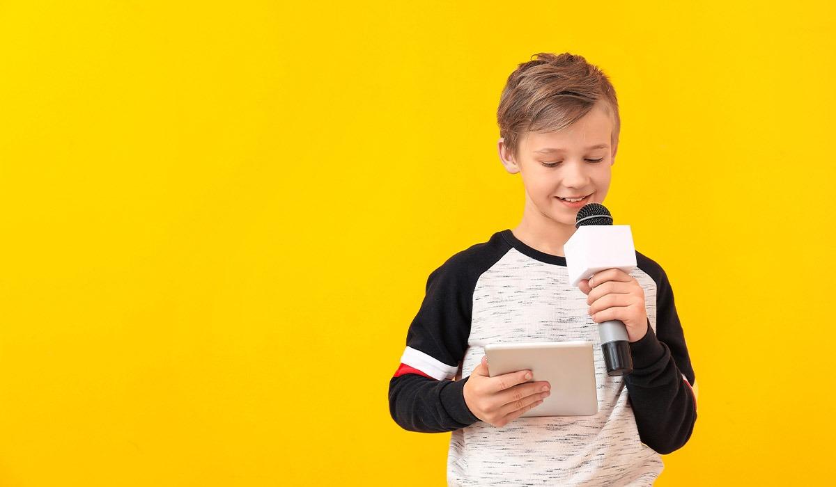 Das Foto zeigt einen Jungen. Er hält ein Mikrofon und ein Tablet in der Hand und liest auf dem Tablet.
