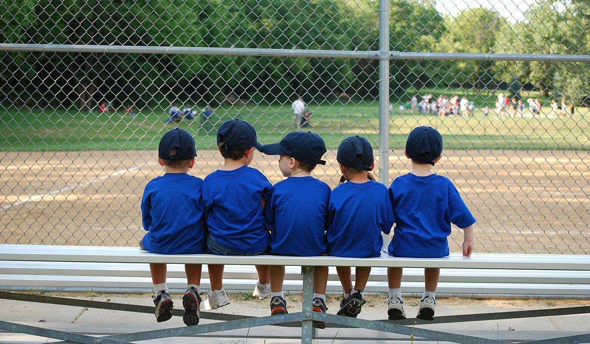 Das Foto zeigt fünf Jungen. Die Jungen sitzen auf einer Bank und tragen blaue T-Shirts. Im Hintergrund sieht man einen Park.